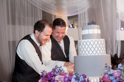 Two grooms cutting cake at Philadelphia wedding
